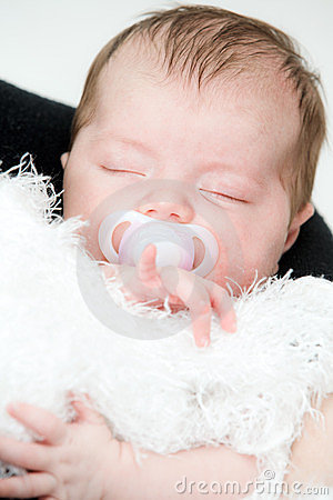 Newborn sleeping child on white blanket