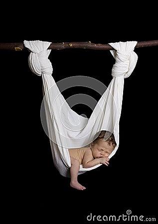 Newborn sleeping peacefully in white hammock