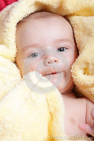 Newborn in soft yellow blanket