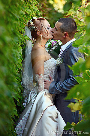 Newly-married couple kisses in a vineyard