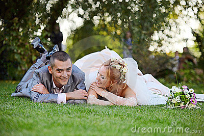 Newly-married couple lies on a grass