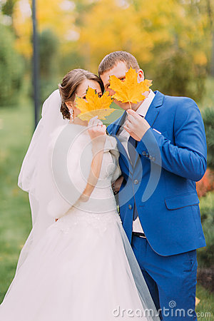 Free Newly Married Couple Posing Outdoors. Young People Hiding Their Faces Behind Autumn Leaves Royalty Free Stock Photography - 72702377