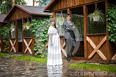 Newly married couple standing in wooden alcove in rainy weather