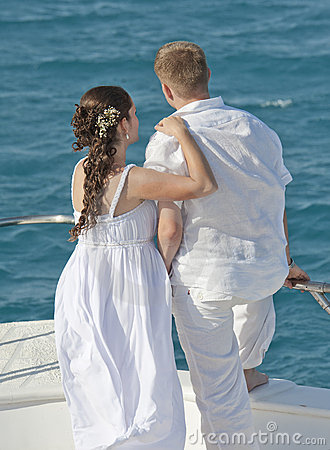 Newly married couple stood on the bow of a boat