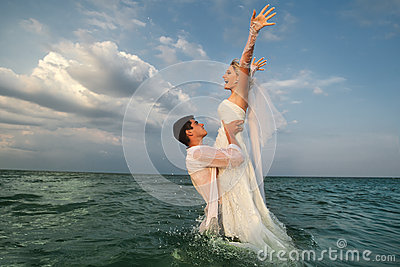 Newly-married couple swimming in sea