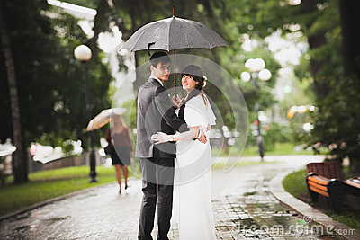 Newly married couple walking in park under rain