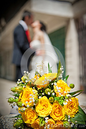Newly-married couple and wedding bouquet