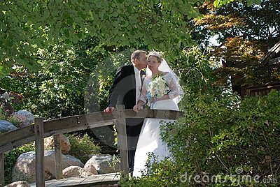 Newly Wed Couple Kiss on Bridge