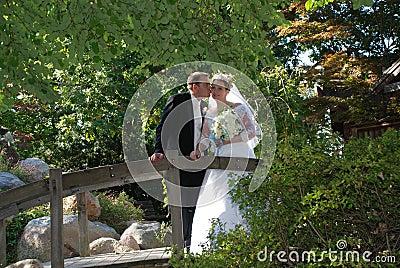 Newly Wed Couple Kiss on Bridge