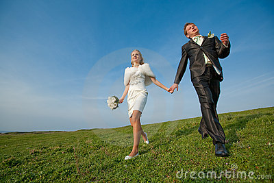 Newly wedded running along the field