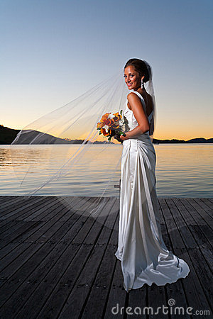Newlywed bride at sunset with veil extended