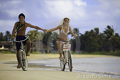 Newlywed couple at beach on bikes