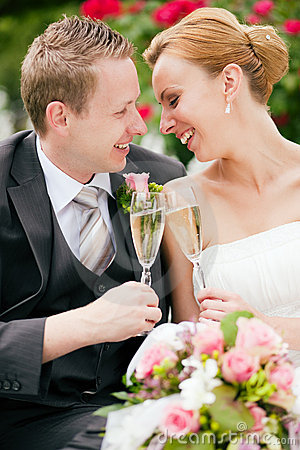 Newlywed couple clinking glasses