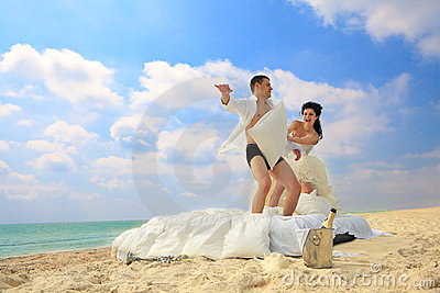 Newlywed couple fighting with pillows