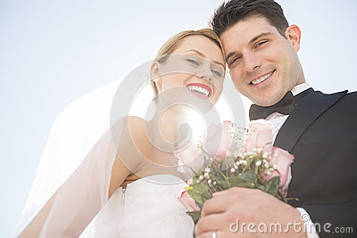 Newlywed Couple With Flower Bouquet Smiling Against Clear Sky