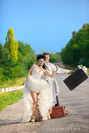Free Newlywed Couple Hitchhiking On A Road Royalty Free Stock Photos - 20899098