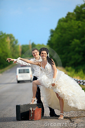 Newlywed couple hitchhiking on a road