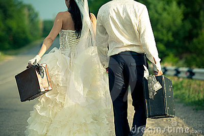 Newlywed couple holding  suitcases of cash