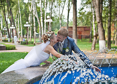 Newlywed couple kissing near fountain