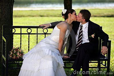 Newlywed couple kissing in park bench