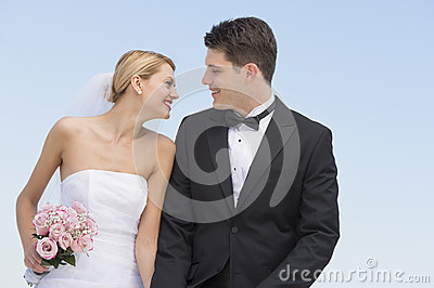 Newlywed Couple Looking At Each Other Against Clear Blue Sky