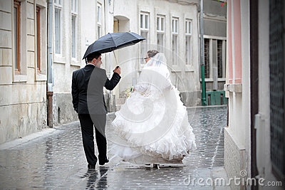 Newlywed couple in rain