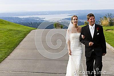 Newlywed couple walking on sidewalk
