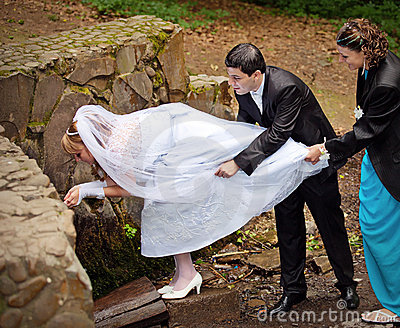 Newlyweds drink water from a spring in the woods