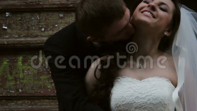 Newlyweds. groom kisses the bride. Near the old door. groom kisses the bride stock footage