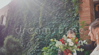 The newlyweds joyously dance at the brick wall with growing branches of grapes. The groom in the dance kisses his bride. With a bright bouquet in his hands. A stock video footage