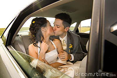 Newlyweds kissing in limo