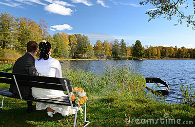 Newlyweds on a lake bench