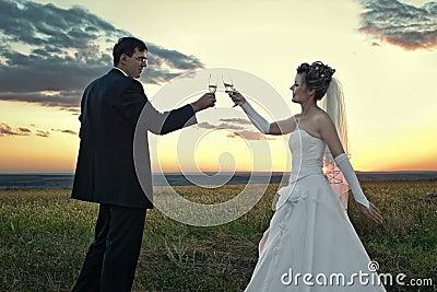 Newlyweds making a toast at dawn