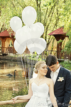 Newlyweds in park with balloons