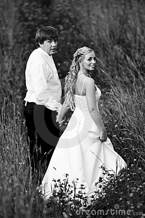 Newlyweds walking in meadow