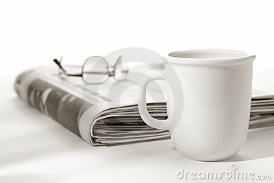 Newspaper with Glasses on Top and Cup of Coffee
