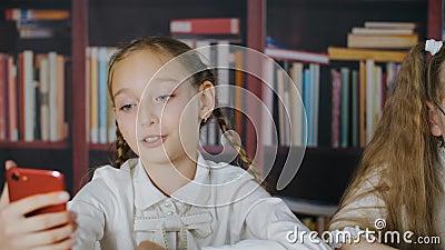 Niña adolescente hablando con suscriptores en video blog por teléfono móvil en clase escolar Blogger girl grabando la historia pa almacen de metraje de vídeo