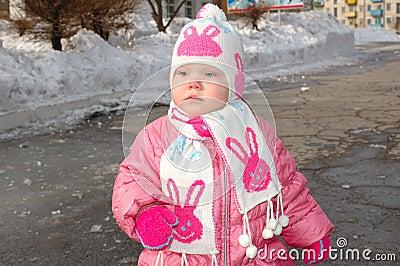 Niña bonita en prendas de vestir exteriores del invierno.
