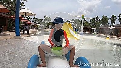 Niña cabalgando en el carro acuático y salpicando agua en el parque de diversiones acuático metrajes