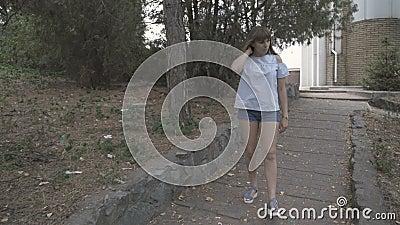 Niña camina por el parque metrajes