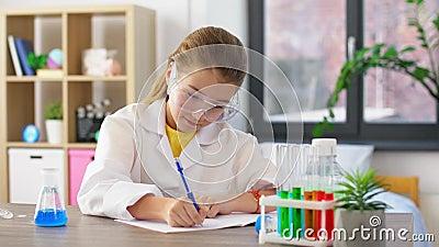 Niña con tubos de ensayo estudiando química en casa almacen de video
