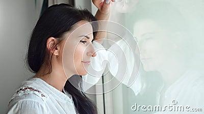 Niña de la mañana relajada durante la vista a través de un cristal transparente desde el interior sensación de calma cerrada metrajes