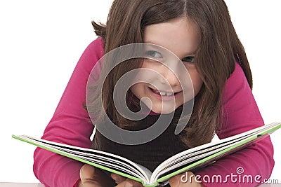 Niña hermosa que lee un libro y una sonrisa