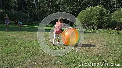 Niña linda que juega con una bola inflable del arco iris colorido grande almacen de video