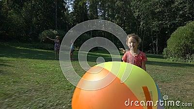 Niña linda que juega con una bola inflable del arco iris colorido grande metrajes