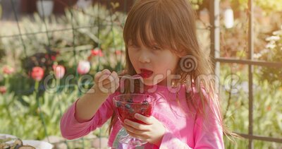 Niña pequeña de 6 ó 7 años comiendo postre de fruta gelatina en el jardín de verano Vídeo en cámara lenta almacen de metraje de vídeo