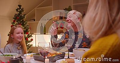Niña pequeña rubia Navidad cena familia risa alegría regalos almacen de metraje de vídeo