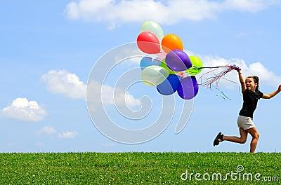 Niña que se ejecuta con los globos