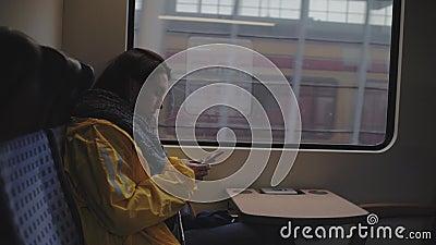 Niña sentada en un tren en movimiento cerca de la ventana con un teléfono mujer con impermeable amarillo Vídeo de 4k 59 94 fps almacen de metraje de vídeo