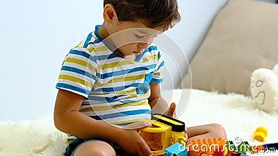 Niño asiático en cámara lenta jugando con coloridos bloques de plástico de construcción en la cama blanca en casa metrajes